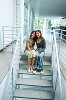 Mother and teenage girl together, sitting on steps, smiling at camera, full length