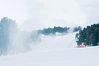 Ski slopes, artificial snow being sprayed