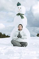 Young man meditating in front of snowman