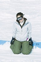 Teenage girl kneeling in snow with snowboard, looking at camera