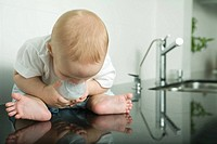 Baby sitting on kitchen counter, holding bottle, looking down at reflection