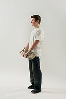 Teenage boy 14-15 holding skateboard, side view