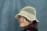 Teenage girl wearing sun hat, smiling over shoulder at camera, portrait