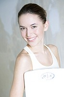 Young woman holding bathroom scale, smiling at camera, portrait