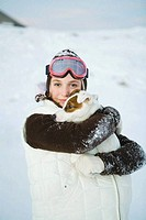 Teenage girl embracing dog, dressed in winter clothing, smiling at camera, portrait