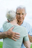 Senior couple hugging, man looking at camera