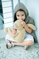 Little girl sitting on floor, whispering into teddy bear´s ear, full length
