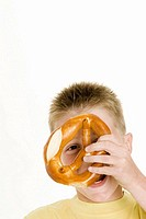 Boy holding a pretzel in front of his face