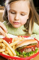 Girl eating chips with ketchup and hamburger