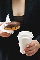 Woman holding doughnut and plastic coffee cup