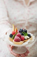 Woman holding berry tarts on cake stand