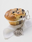 Blueberry muffin in paper case, cake tongs beside it