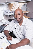 Mature man wearing headset sitting at desk in office, portrait