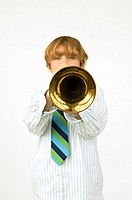 Boy 12-14 blowing trumpet, portrait