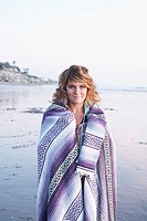 Woman wrapped in blanket on beach, portrait