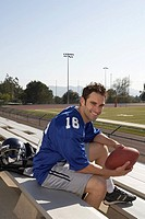 American football player sitting on bleachers holding football, portrait