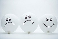 Three white balloons with happy and sad faces
