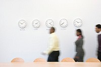 Men and women walking across office with clocks on wall, blurred motion