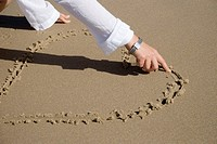 Woman drawing a heart on beach sand