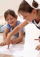 Girls, paper, pens, floor,