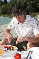 Man, plates, vegetables, river, shore, sit, picnic,