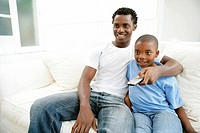 Young African Boy Watching Television with his Father  Cape Town, Western Cape Province, South Africa
