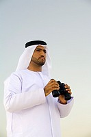 Arab Man Looking into the Distance With Binoculars  Dubai, United Arab Emirates
