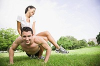 Man doing push-ups with his girlfriend on his back (thumbnail)