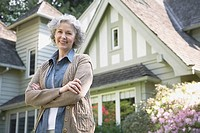 Confident woman in front of house