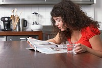 Woman reading magazine in kitchen