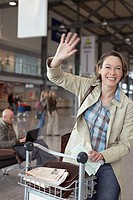 Woman waving in airport