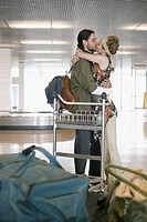Man and woman kissing in airport