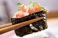 Sushi roll with shrimps in chopsticks