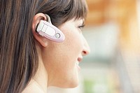 Woman wearing cell phone headset on ear