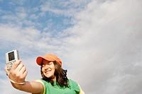 Latino woman holding digital camera.