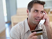 Man with credit card on telephone