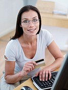 Woman with credit card and eyeglasses at computer smiling