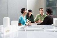 Four businesspeople in an office by a city model