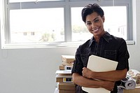 Businesswoman holding folder in office (thumbnail)