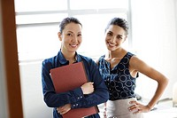Two businesswomen standing indoors smiling