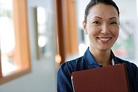 Businesswoman holding paperwork indoors smiling