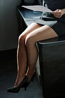 Businesswoman's legs dangling off desk