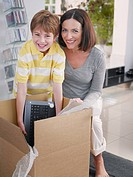 Woman and young boy opening box with computer inside