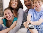 Couple with young boy and girl on sofa with television remote