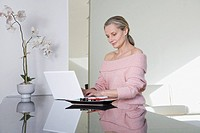 Woman working on laptop in modern home