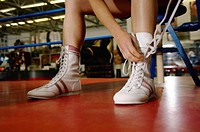 Boxer tying up boots in boxing ring