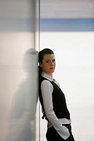 Stylish businesswoman leaning against wall (thumbnail)