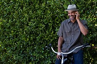 Man on cellular phone sitting on a bicycle