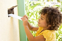 Girl putting mail through a mail slot in door