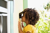 Girl peeking through a mail slot in door